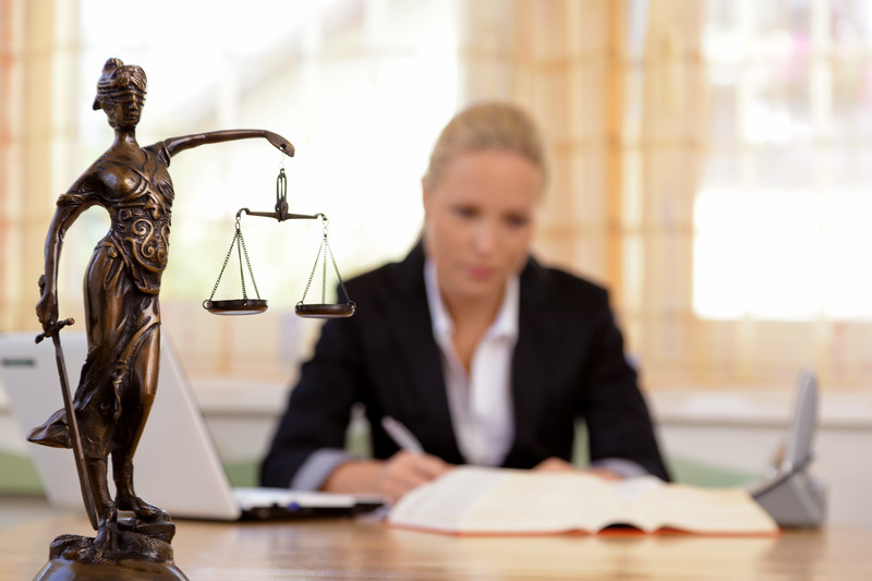 Lawyer working and referring to legal text with a small statue of justice in the forefront